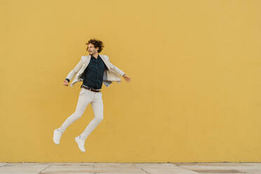 Businessman jumping in the air in front of yellow wall - AFVF03415