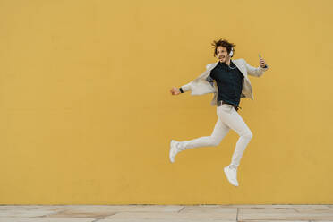 Businessman jumping in the air in front of yellow wall listening music with headphones and smartphone - AFVF03418