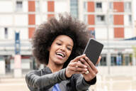 Happy young woman with afro hair in city, taking smartphone selfie - CUF51476