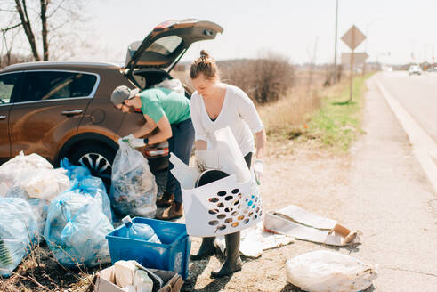 Couple picking up rubbish by roadside, Georgetown, Canada - ISF21810