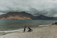 Mother with baby in pram walking on beach, Queenstown, Canterbury, New Zealand - ISF21819