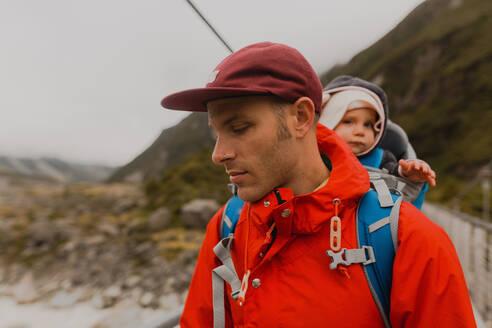 Hiker with baby on suspension bridge, Wanaka, Taranaki, New Zealand - ISF21855