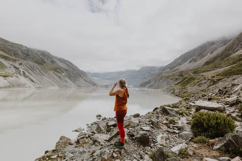 Woman enjoying scenic view by lake, Wanaka, Taranaki, New Zealand - ISF21873