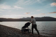 Mother with baby in pram walking on beach, Te Anau, Southland, New Zealand - ISF21879