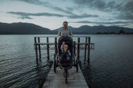 Mother with baby in pram on bridge by seaside, Te Anau, Southland, New Zealand - ISF21882