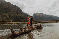 Parents and baby on fallen tree in lake, Queenstown, Canterbury, New Zealand - ISF21888