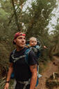 Hiker with baby exploring forest, Queenstown, Canterbury, New Zealand - ISF21903