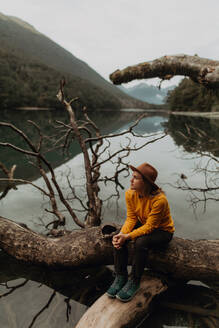 Woman enjoying scenic lake view, Queenstown, Canterbury, New Zealand - ISF21909