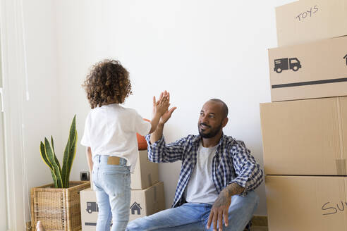 Father and daughter high fiving at new home - JPTF00178