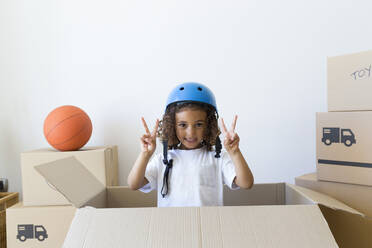 Portrait of girl wearing bicycle helmet looking out of cardboard box at new home - JPTF00181