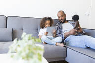 Father and daughter sitting on couch at home with doll and tablet - JPTF00184