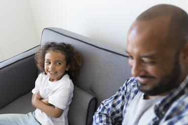 Happy father and daughter sitting on couch at home - JPTF00190
