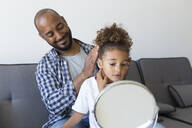 Father doing daughter's hair on couch at home - JPTF00193