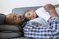 Father and daughter sleeping on couch at home - JPTF00199
