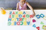 Girl playing with alphabet learning game at home - JPTF00202
