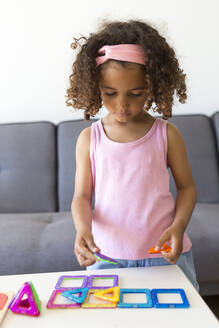Girl playing with learning game at home - JPTF00205