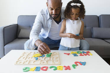 Father and daughter playing with alphabet learning game at home - JPTF00208