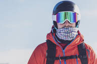 Man with ski goggles and skiing helmet in front of light background, Saalbach Hinterglemm, Pinzgau, Austria - MMAF01064