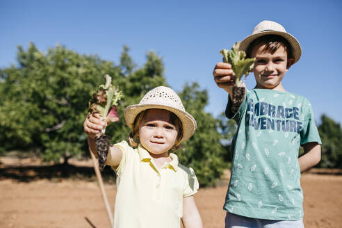 Spain, Tarragona. Brother and sister showing the vegetables they are going to plant this sunny day - JRFF03387