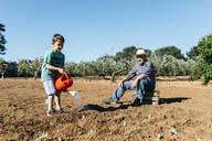 Grandfather and grandson watering freshly planted vegetables - JRFF03399