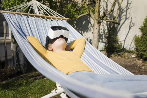 Girl lying in hammock in garden wearing VR glasses - MOEF02275