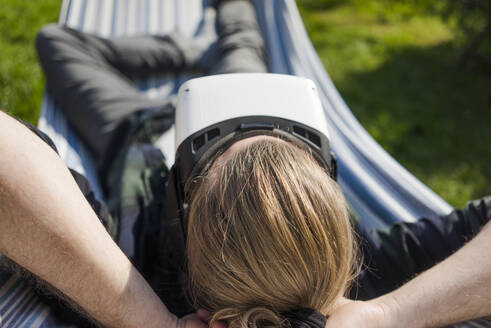 Man lying in hammock in garden wearing VR glasses - MOEF02278
