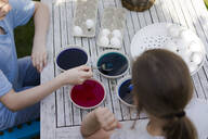 Two girls dyeing Easter eggs on garden table - MOEF02287