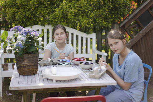 Portrait of two girls dyeing Easter eggs on garden table - MOEF02293