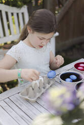 Girl dyeing Easter eggs in garden - MOEF02296