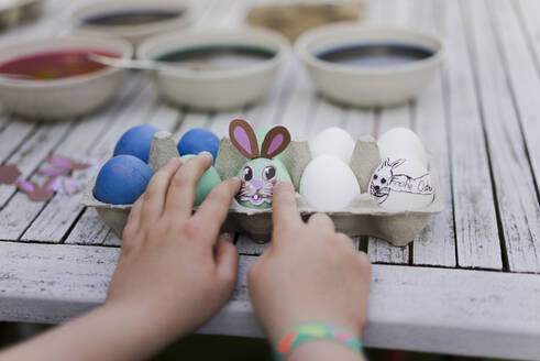 Close-up of girl decorating Easter egg on garden table - MOEF02299