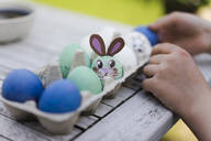 Close-up of girl decorating Easter egg on garden table - MOEF02302