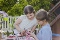 Two girls painting Easter eggs on garden table - MOEF02305