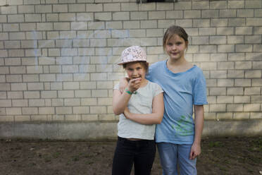 Portrait of two girls standing in front of a brick wall - MOEF02308