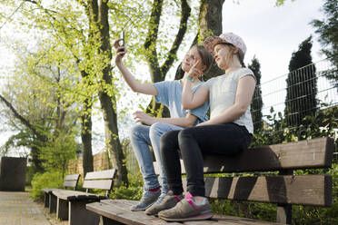 Two girls sitting on a park bench taking a selfie - MOEF02311