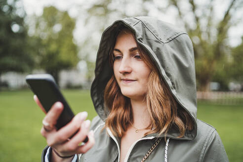 Young woman wearing hooded jacket and using cell phone on a rainy day - FBAF00776