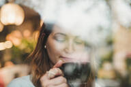 Young woman in a cafe drinking coffee behind windowpane - FBAF00788