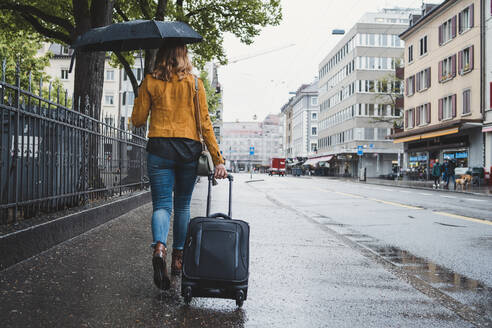 Young woman walking in the city on a rainy day, Zurich, Switzerland - FBAF00791
