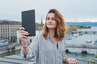 Young woman taking smartphone picture at Lake Zurich, Zurich, Switzerland - FBAF00803
