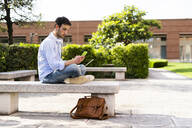 Young man using laptop and smartphone, headphones around neck, sitting on a bench - GIOF06518
