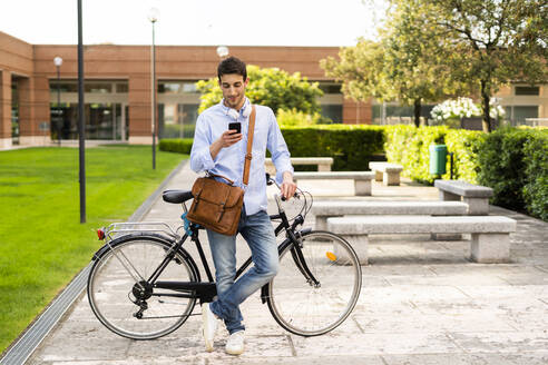 Young man with bicycle using smartphone, headphones around neck in the city - GIOF06521