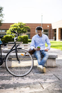 Young man with bicycle using smartphone and listening music - GIOF06527