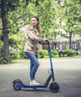 junge Frau mit e - scooter, Elektroroller, Roller, Elektro-Mobilität, Umweltschutz, lifestyle, Berlin, Deutschland - BFRF02025