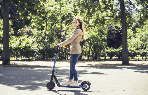 Portrait of smiling woman with E-Scooter - BFRF02031