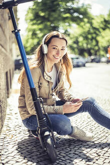Portrait of smiling woman sitting on E-Scooter listening music with headphones and smartphone - BFRF02037