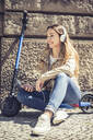 Smiling woman sitting on E-Scooter listening music with headphones and smartphone - BFRF02040