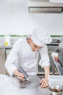 Junior chef prepairing a dessert plate - LJF00176