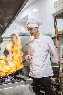 Junior chef with pan of flames in traditional spanish restaurant kitchen - LJF00200