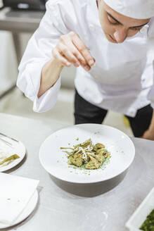 Junior chef prepairing a dessert on plate - LJF00206