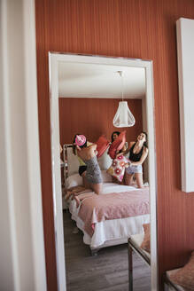Girlfriends celebrating birthday, pillow fight on the bed, mirror - LJF00209