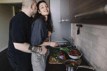 Man hugging and kissing woman in the kitchen - EYAF00265